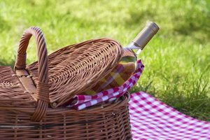 A bottle of white wine peeking out of a wicker basket on a red gingham tablecloth in the grass.