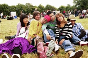 A group of teenagers hanging out in the grass at a festival.