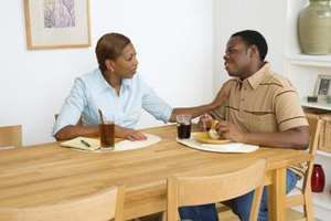 Mother talking to son at kitchen table