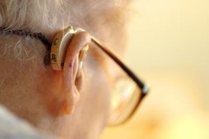Profile of elderly man with a hearing aid.