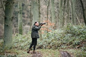 Hunter holding up gun in the forrest.