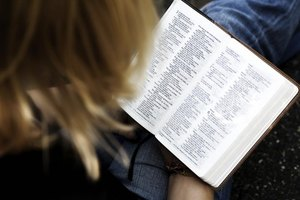 An overhead view of a woman studying the Bible.