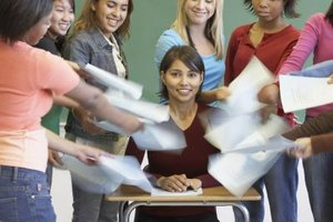 Students handing in papers to teacher at desk