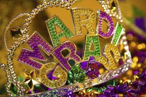 A close-up of a Mardi Gras decorative crown on a party table.