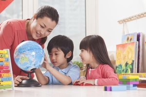 Children looking at globe with teacher