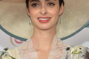 Actress Krysten Ritter wears a floral dress with a large floppy hat at the Kentucky Derby.