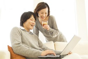 A young couple is using a laptop together.
