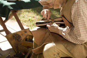 A colonial cobbler sitting on a stool outside while constructing a shoe.