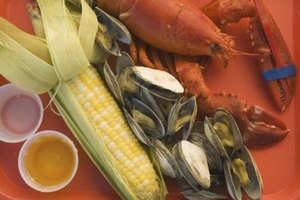 A traditional Maine lobster dinner includes steamed clams and grilled corn.