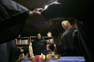 Wiccans and their high priestess join hands for a Lunar festival.