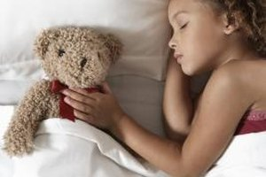 Some children need comforting tactile experiences, like petting a toy bear, to relax before sleep.