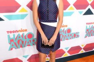 Actress Nikki Reed accents her purple dress with bright white pumps.