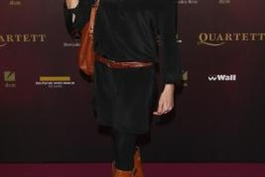 German actress Bettina Zimmermann makes her outfit feel intentional by pairing a black dress with a cognac belt, bag and boots.