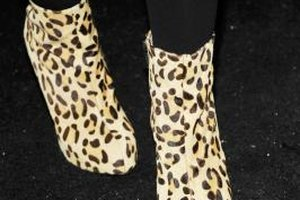Pair leopard print ankle boots with tights for a stylish ensemble.