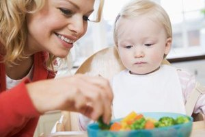 A baby builds self-feeding skills gradually.