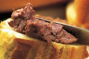 Spread homemade deer liver pate on fresh slices of French bread for a savory snack.