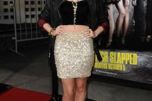Actress Claudia Lee pairs a gold sequined skirt with a black crop top and leather jacket.
