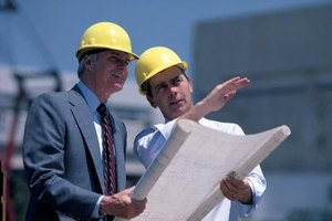 An engineer consultant discusses plans with a company manager.