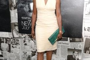 Actress Adina Porter sports a cream-colored dress with strappy silver heels.