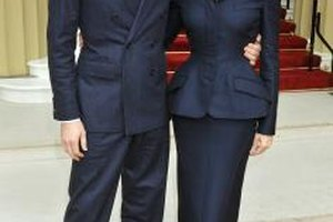 Designer Stella McCartney wears a chic black suit with husband Alasdhair Willis to Buckingham Palace in London.