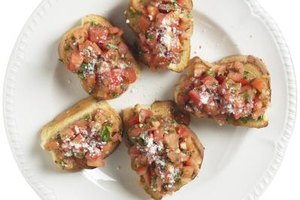Serve warm bruschetta topped with seasonings and bubbly cheese.