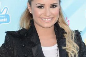 Demi Lovato goes for a casual look with her black lace blazer by pairing it with a simple white tee.