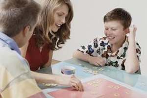 Families may grow closer by spending time enjoying a family game night.