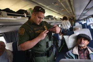 A Border Patrol agent checks a passenger's ID on an Amtrak trip.