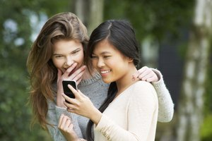 Image of teenage girls reading a text message.