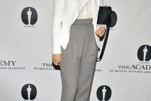 Actress Marisa Tomei pairs gray pinstripe pants with a white button-down blouse and jacket for a stylish, polished look.