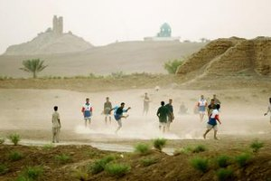 The ruins of a ziggurat built by Nebuchadnezzar rise in the distance behind an Iraqi soccer game.