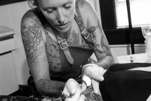 Tattoo artists are part of the body art job market.