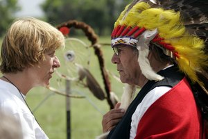 Dennis Banks, a founder of the American Indian Movement, in headdress, meets with a political activist.