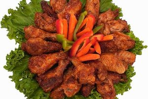 Buffalo chicken wings are first fried then rolled in a hot sauce mixture.
