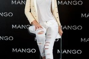 Model Miranda Kerr paired white ripped jeans with matching tank and pumps for a sexy monochromatic outfit.