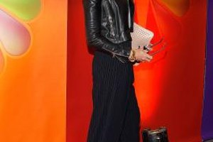 Elle McPherson keeps her look simple and chic by pairing her pinstriped pants with a black top.