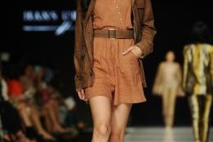 A model walking in an Erasmus Huis fashion show rocks a brown leather jacket with a flirty dress.