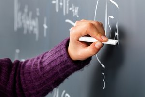 Close-up of hand writing math problem on chalkboard