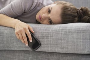 A frustrated woman laying on the couch with her smart phone.