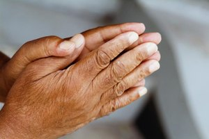 A close-up of a woman's hands pressed together in prayer.