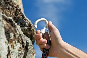 A rock climber clips a carabiner into a hook on the side of a mountain.