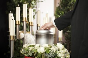 Man resting hand on cremated ashes at funeral