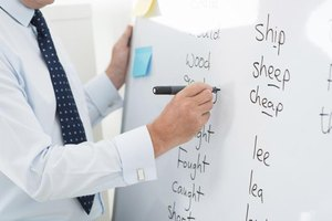 Close-up of an English teacher writing words on a marker board