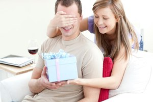 Woman covering boyfriend's eyes while handing gift to him