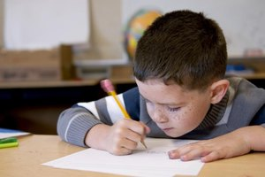 An elementary student writing at a classroom table.