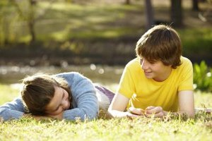 Friends talking as they lay on grass field.
