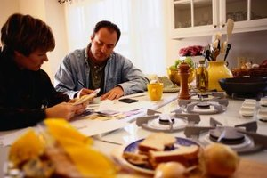 A couple manages their finances on the kitchen table.