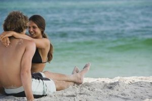Young couple holding onto each other at beach.