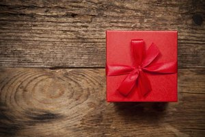 A red gift box on a wooden table.