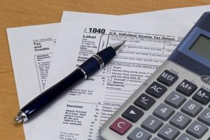 Income tax form with calculator and pen.